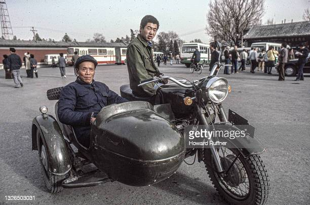 Portrait of two unidentified men as they pose with their motorcycle with a sidecar, near the entrance of the Great Wall of China, Beijing, China,...