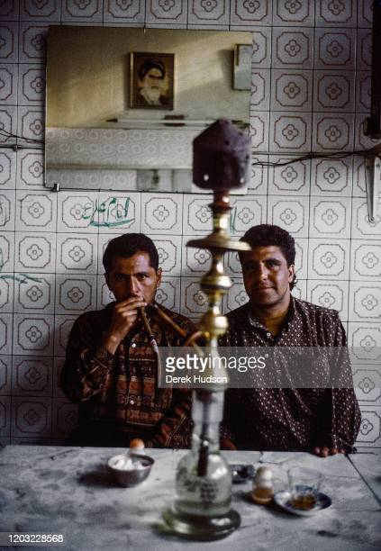 Portrait of two unidentified men as they sit at a behind a water pipe in a tea shop Shiraz Iran 1998 On the wall behind them is a mirror which...