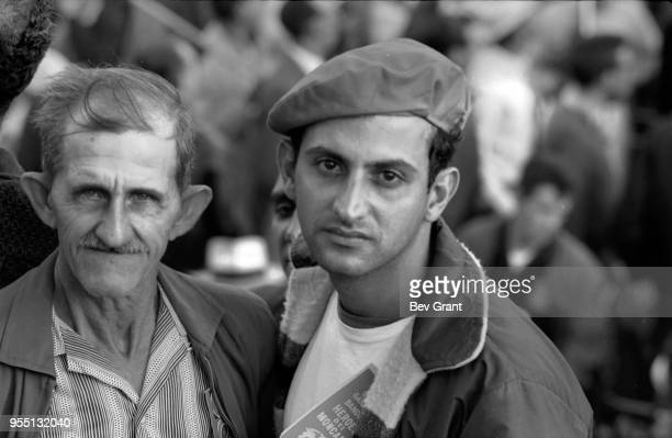 Portrait of two unidentified men one elderly and the other in a beret in the audience in la Plaza de la Revolucion during the 10th anniversary...