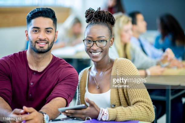 portrait of two university students working together in class - community college stock pictures, royalty-free photos & images