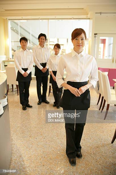 Portrait of two waiters and two waitresses standing in a restaurant