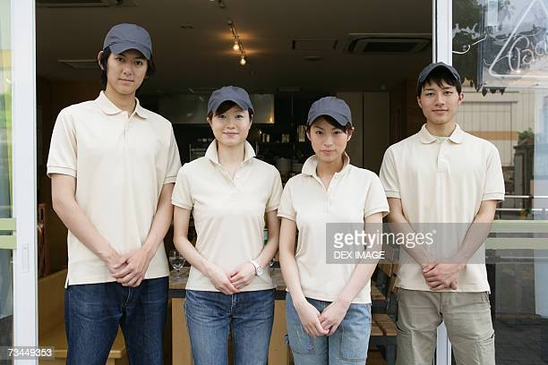 portrait of two waiters with two waitresses standing in front of a restaurant - ポロシャツ ストックフォトと画像