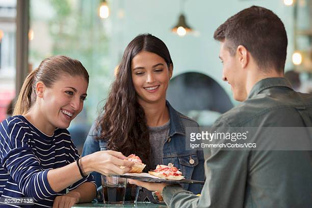Portrait of two women and man eating sandwiches at cafe