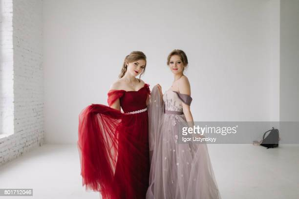 portrait of  two women dancing in prom dresses   in studio - prom dress stock pictures, royalty-free photos & images