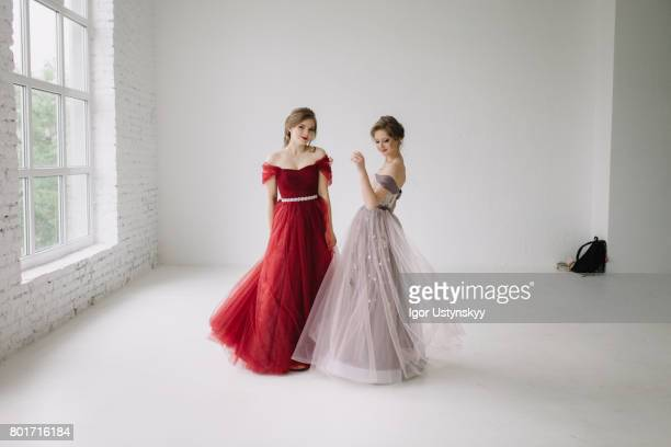 Portrait of  two women dancing in prom dresses   in studio