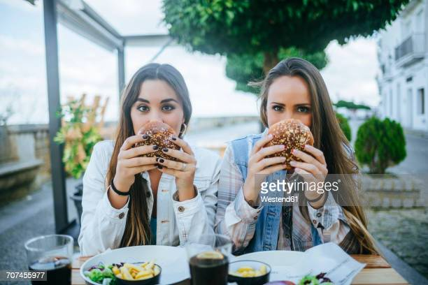 Portrait of two women holding hamburgers in a street restaurant