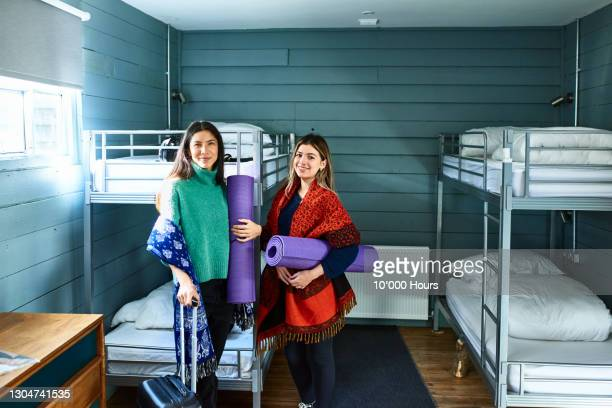 portrait of two women in hostel dormitory with yoga mats - finance and economy stock pictures, royalty-free photos & images