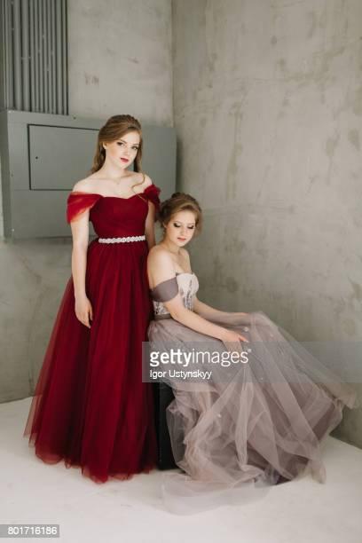 Portrait of  two women in prom dresses   in studio