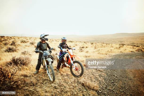 Portrait of two women riding dirt bikes in desert on summer evening