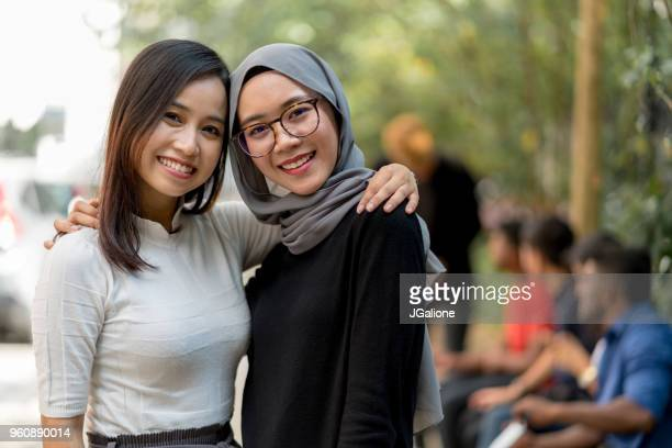 portrait of two women smiling - malaysian culture stock pictures, royalty-free photos & images