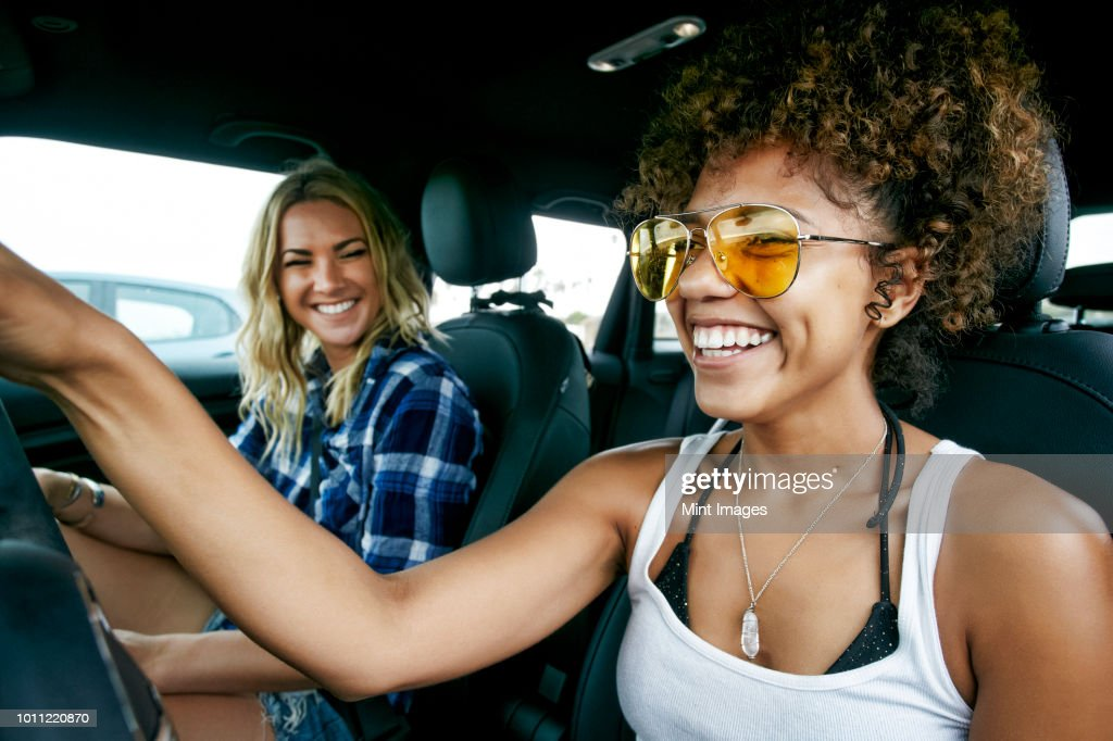 Portrait of two women with long blond and brown curly hair sitting in car, wearing sunglasses, smiling. : Stock Photo