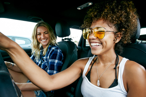 Portrait of two women with long blond and brown curly hair sitting in car, wearing sunglasses, smiling. - gettyimageskorea