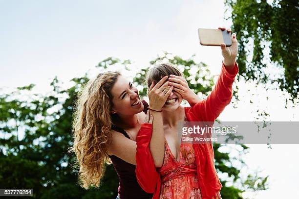 portrait of two young adult women taking a selfie in the park