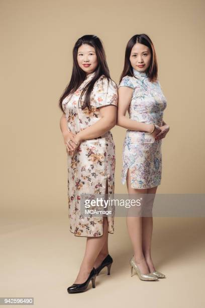 Portrait of two young Asian women in traditional cheongsam