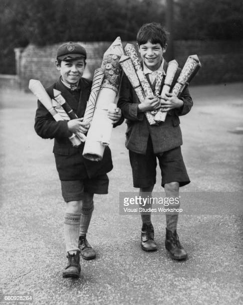Portrait of two young boys as they smile their arms full of oversize firework rockets 1920s or 1930s