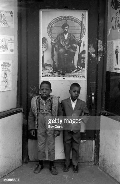 Portrait of two young boys as they stand in front of the Black Panther Party's Harlem office, New York, New York, winter 1969. A poster of Huey...