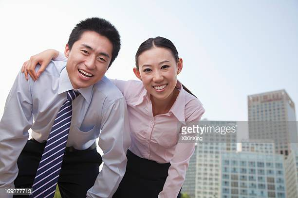 Portrait of two young business people leaning forward, outside in the business district, Beijing