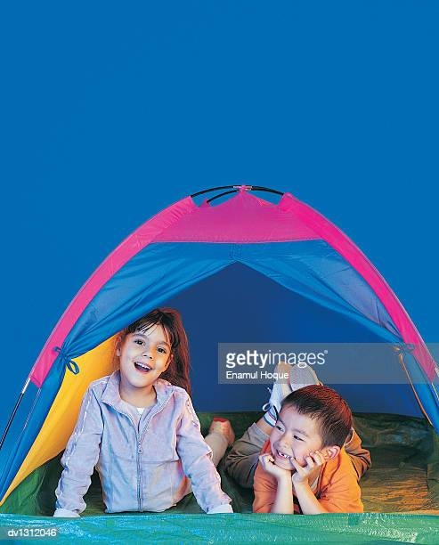 Portrait of Two Young Children Lying in a Tent
