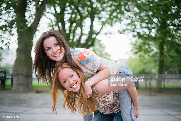 Portrait of two young female best friends giving piggy back in park
