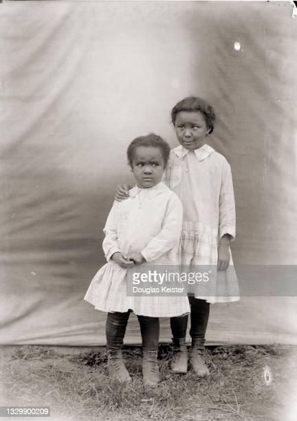 Portrait of two young girls, in matching outfits , as they pose in front of a backdrop, Lincoln, Nebraska, early 20th century.