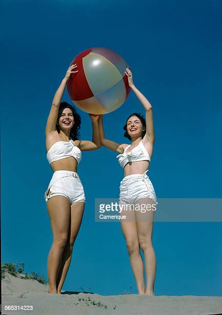 Portrait of two young girls in white bathing suits holding a large beach ball Los Angeles California 1950