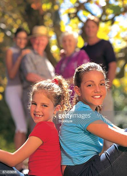 portrait of two young girls (4-8) sitting back to back smiling