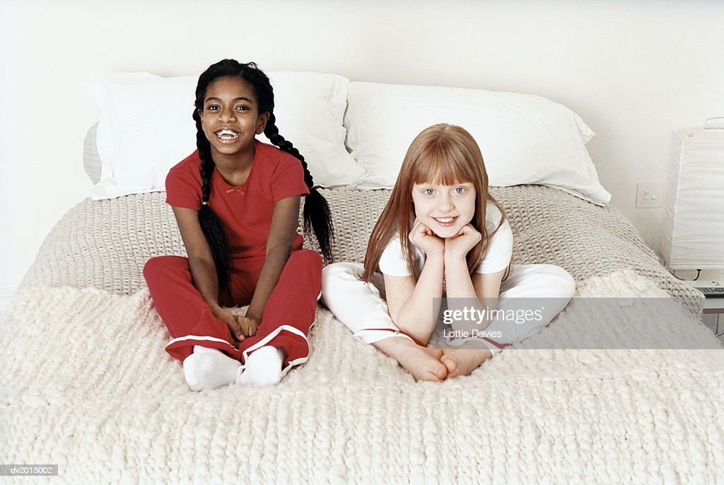 Portrait of Two Young Girls Sitting on Bed : Stock Photo