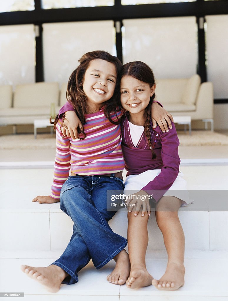 Portrait of Two Young Girls Sitting Side by Side on Patio Steps : Stock Photo