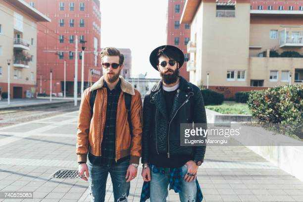 Portrait of two young male hipster friends standing in city housing estate