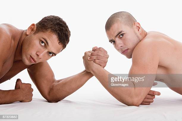 Portrait of two young men arm wrestling