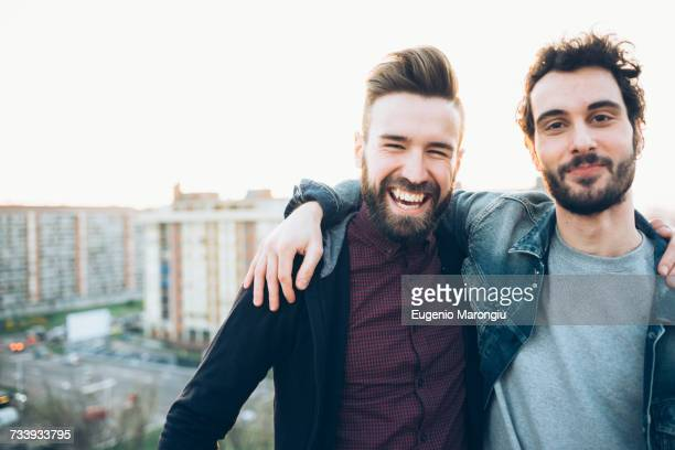 portrait of two young men, on roof, smiling - arm around stock pictures, royalty-free photos & images