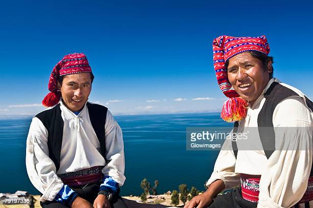portrait of two young men sitting, taquile island, lake titicaca, puno, peru - traditional clothing stock photos and pictures
