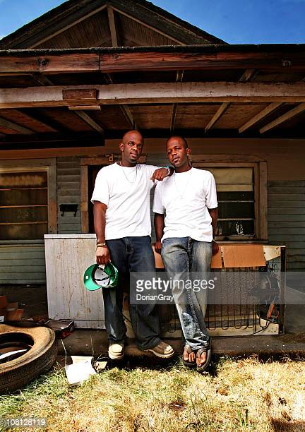 Portrait of Two Young Men Standing Outside Run Down House