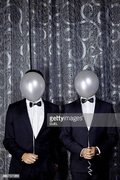 Portrait of two young men with balloons in front of faces