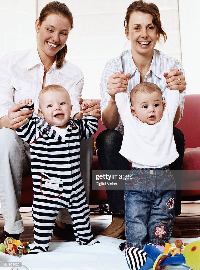 Portrait of Two Young Mothers with Their Babies : Stock Photo