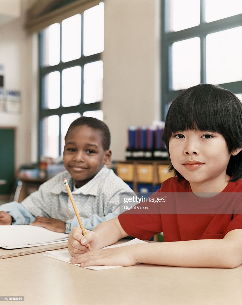 Portrait of Two Young Schoolboys Sitting at a Desk in a Classroom : Stock Photo