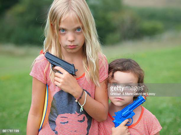 Portrait of two young sisters, holding toy guns