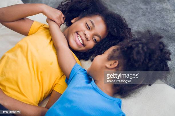 portrait of two young sisters lying face to face in bed - children only stock pictures, royalty-free photos & images