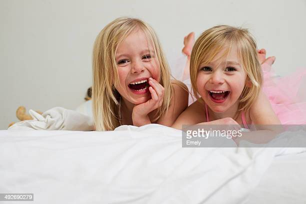 Portrait of two young sisters lying on front in bed