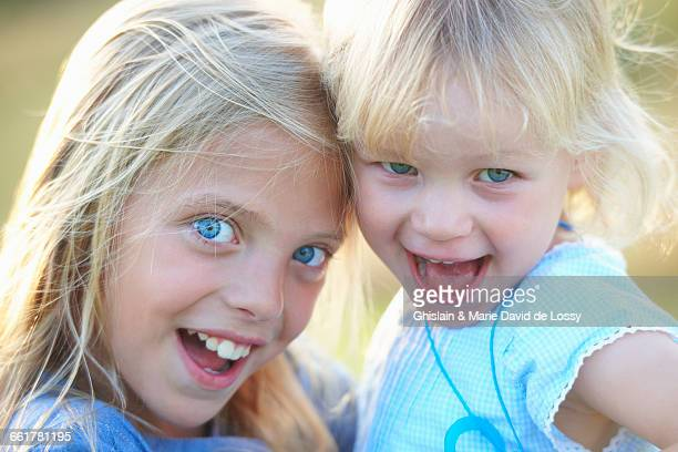 Portrait of two young sisters, outdoors, smiling