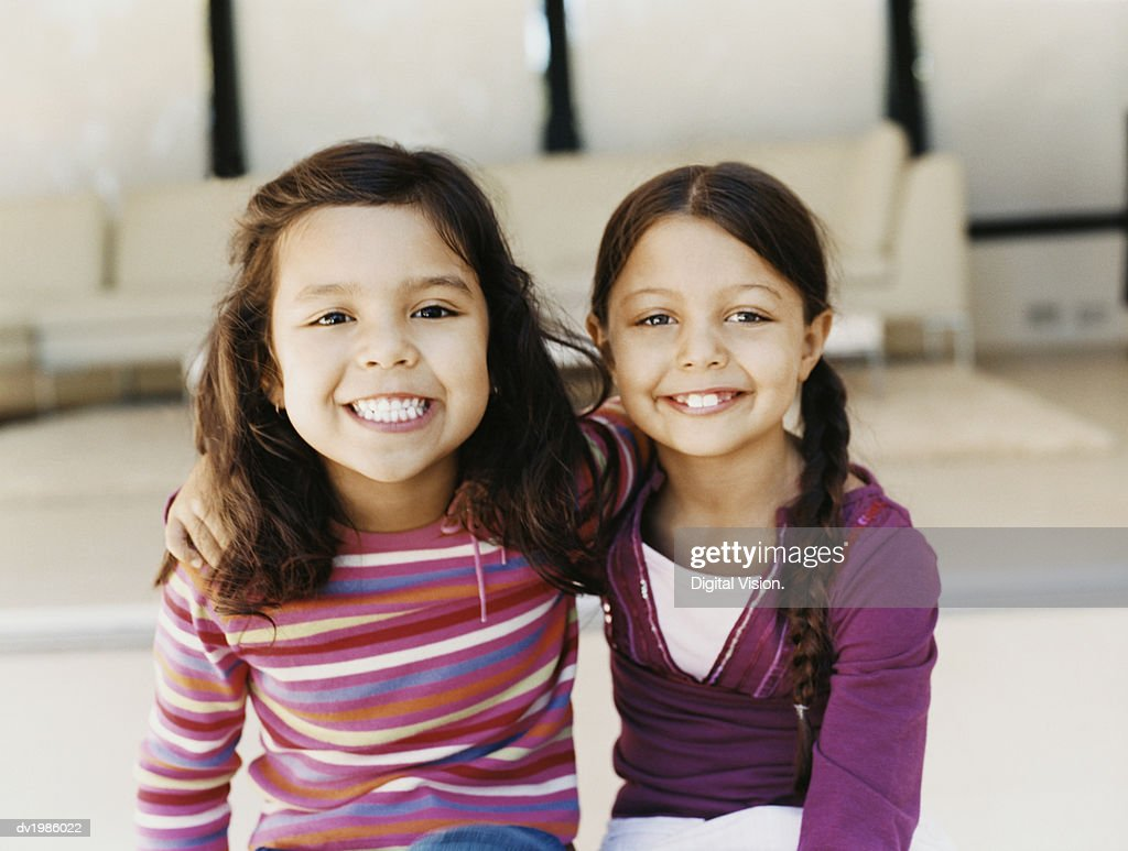 Portrait of Two Young Sisters Sitting Side by Side : Stock Photo