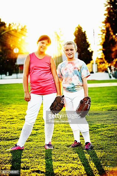Portrait of two young smiling softball teammates