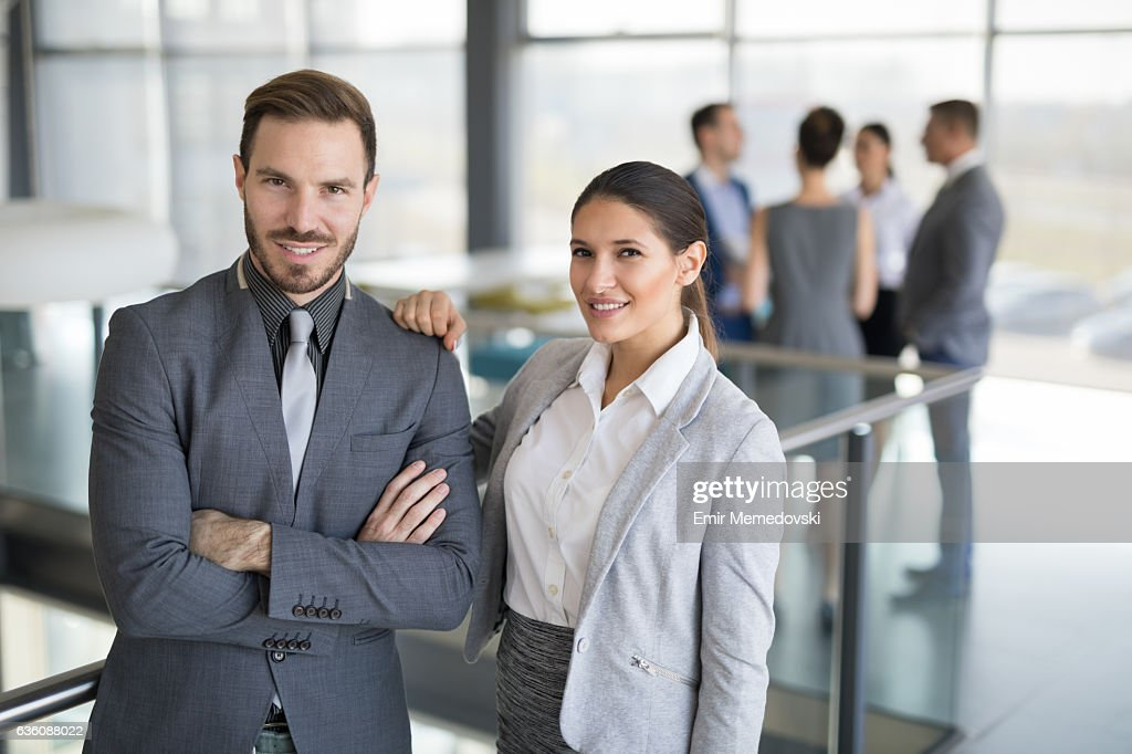 portrait of two young successful business people at work stock photo