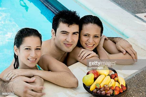 Portrait of two young women and a young man in a swimming pool