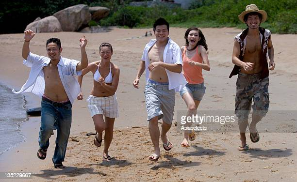 Portrait of two young women and three young men running on the beach