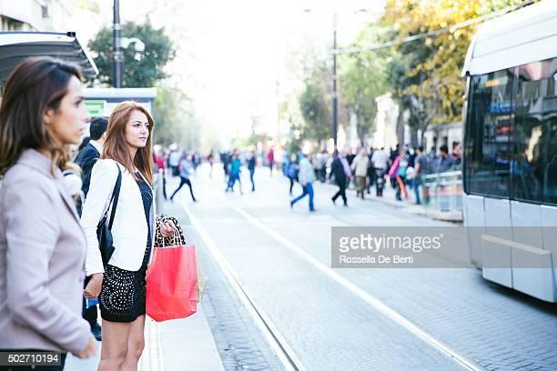 Portrait de deux jeunes femmes à l'arrêt de tramway