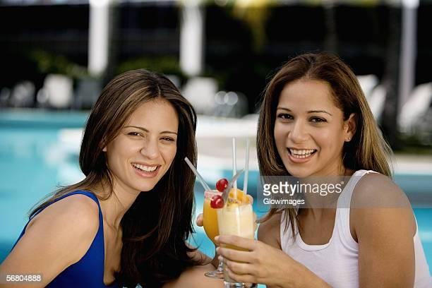 Portrait of two young women holding juice glasses