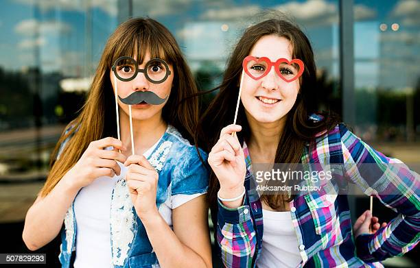 Portrait of two young women holding up mustache and eyeglass costume masks