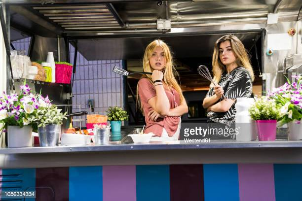 portrait of two young women in a food truck - plastic plate stock photos and pictures