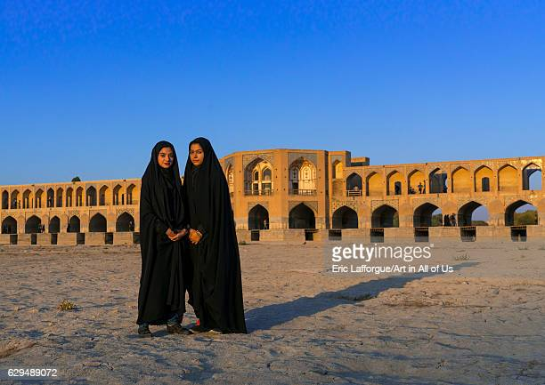 Portrait of two young women in chadors in front of Khaju bridge Pol-e Khaju, Isfahan Province, Isfahan, Iran on October 13, 2016 in Isfahan, Iran.